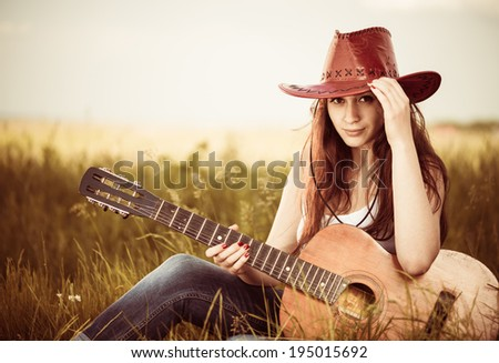 young stylish cowgirl with guitar at spring meadow - stock photo