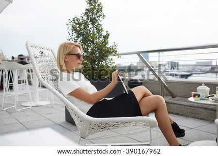 Young stylish female is thinking about something, while is resting after seeing movie on portable touch pad. Gorgeous woman college student is relaxing after reading electronic book on digital tablet - stock photo