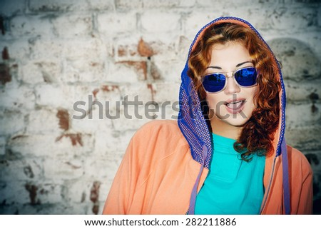 Young stylish girl in the city. Brick wall background. Youth fashion. Hip-hop style. - stock photo