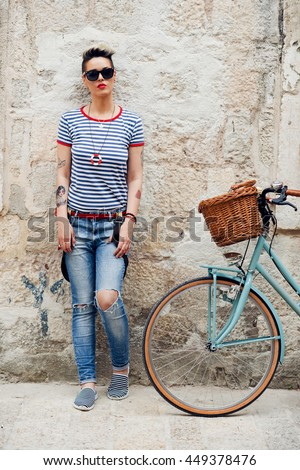 Young stylish girl  leaning on the wall  near her  vintage bike  and looking to the camera - stock photo