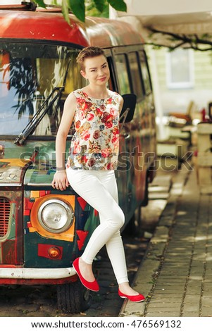 young stylish girl posing and smiling on background of colorful retro bus in fashionable colorful clothes in city street