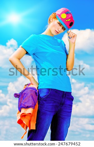 Young stylish girl posing over blue sky. Youth fashion. Hip-hop style. - stock photo