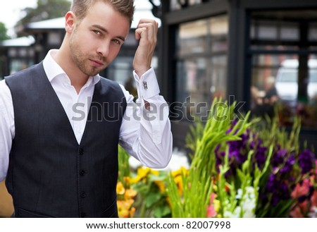 Young stylish guy near outdoor flower store - stock photo