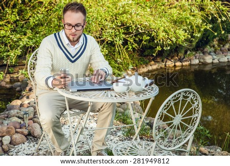 Young stylish handsome man in bright confidential clothes work at  iron table with computer against country garden. - stock photo
