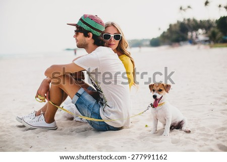 young stylish hipster couple in love walking playing dog puppy jack russell in tropical beach, white sand, cool outfit, romantic mood, having fun, sunny, man woman together? horizontal, vacation - stock photo