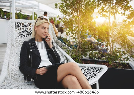 Young stylish hipster girl is talking on mobile phone, while is sitting with digital tablet in comfortable chair on hotel balcony. Fashionable modern businesswoman having cell telephone conversation