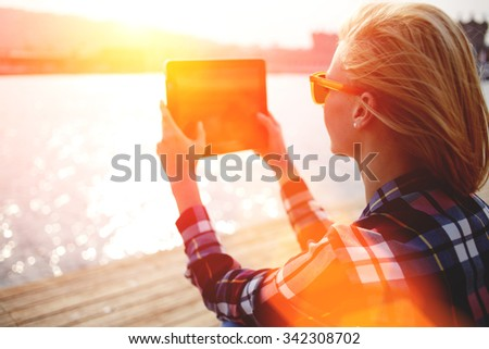 Young stylish hipster girl photographing on digital tablet beautiful sea landscape in summer evening, woman taking photo with touch pad camera while sitting on a river jetty during recreation time  - stock photo