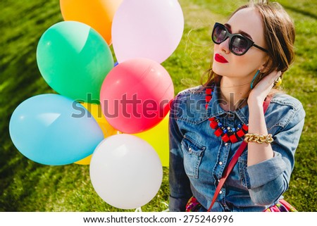 young stylish hipster teen girl happy smiling, park, air balloons birthday party, cool accessories red lipstick, colorful, sunny, have fun, sitting, grass, denim shirt, flower printed skirt sunglasses - stock photo