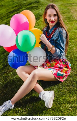young stylish hipster teen girl happy smiling, park, air balloons birthday party, cool accessories, red lipstick makeup, colorful, sunny, have fun, sitting on grass, denim shirt, braces, laughing - stock photo
