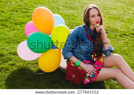 young stylish hipster teen girl happy smiling, park, air balloons birthday party, cool accessories, red lipstick makeup, colorful, sunny, have fun, sitting on grass, denim shirt, horizontal - stock photo