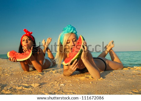 Young stylish ladies at sea with watermelon - stock photo