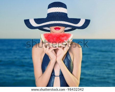 Young stylish lady in a hat at sea with watermelon - stock photo