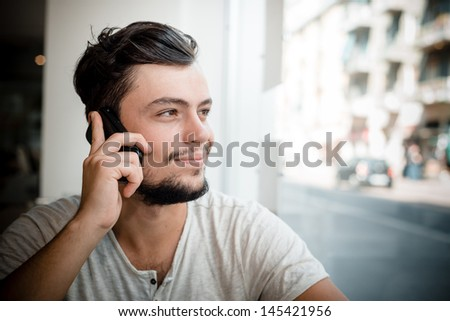 young stylish man at the bar on the phone - stock photo