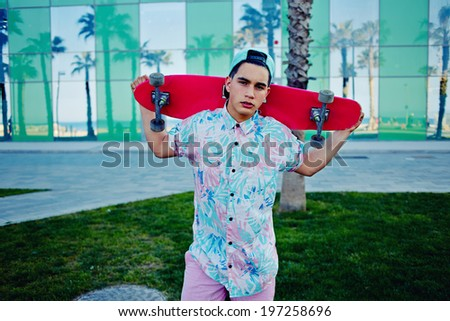 Young stylish man in bright summer clothes standing with a pink long-board - stock photo