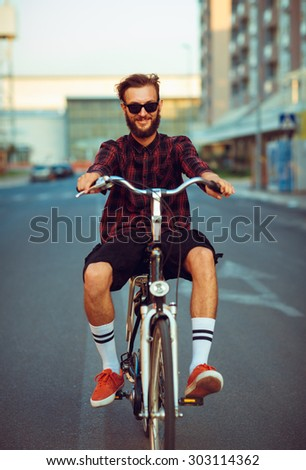 Young stylish man in sunglasses riding a bike on city street - stock photo