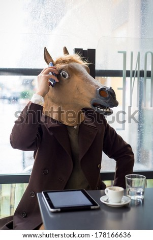 young stylish man lifestyle horse mask at the bar in the city - stock photo