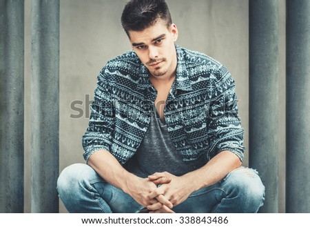 Young stylish man model posing near concrete wall. Fashion. man model sunglasses, man model casual, man model vogue, man model pose, man handsome, man model sexy, man model shirt, man pose, man style - stock photo