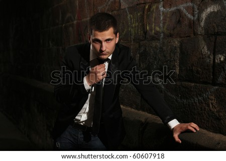 young stylish man standing in dark - stock photo