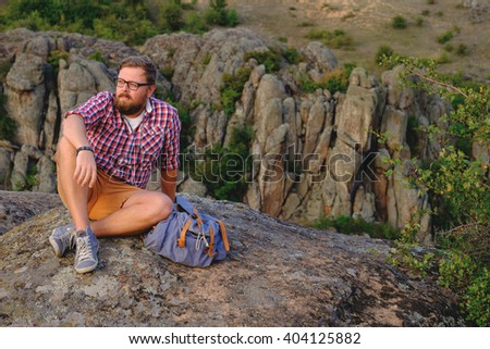 Young stylish man with a beard sitting on a canyon cliff
