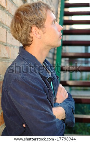 Young stylish man with blonde hair stand near brick wall and stairs.
