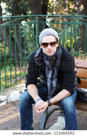 Young stylish man with scarf and beanie sitting on a bench - stock photo