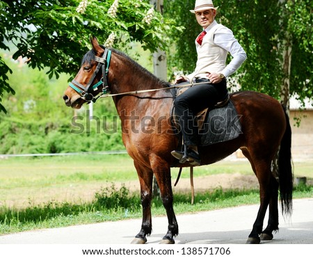 Young stylish man with tie and hat riding a horse on countryside - stock photo