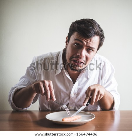 young stylish man with white shirt eating carrot behind a table
