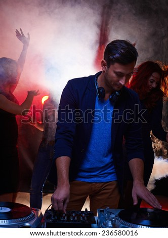 Young stylish man working as deejay in night club - stock photo