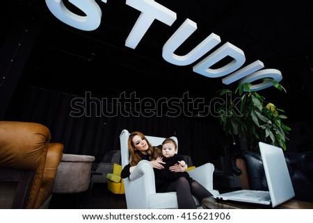 Young stylish  mother with her adorable baby girl in  hipster cafe. A working fashion mom and toddler. Hugging her daughter sitting in a chair in front of computer - stock photo