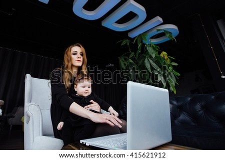 Young stylish  mother with her adorable baby girl in  hipster cafe. A working fashion mom and toddler. Hugging her daughter sitting in a chair in front of computer and working. - stock photo