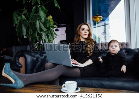 Young stylish  mother with her adorable baby girl in  hipster cafe. A working on laptop fashion mom and toddler. Sitting on a leather couch. - stock photo