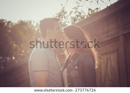 Young stylish pretty couple in love posing outdoor in the city while kissing and having fun in summer at sunset. selective focus on face - stock photo