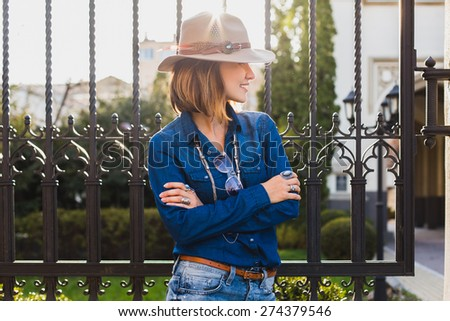 young stylish pretty happy woman smiling and posing, dressed in denim shirt, high heel shoes, hat and backpack, sunny day, good weather, city street, cool accessories, sunglasses, vacation - stock photo
