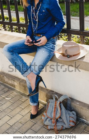 young stylish pretty woman, hands holding a phone, dressed in denim shirt and jeans, high heel shoes, hat, backpack, sunny day, good weather, city street, vacation europe, travel, detail, accessories - stock photo