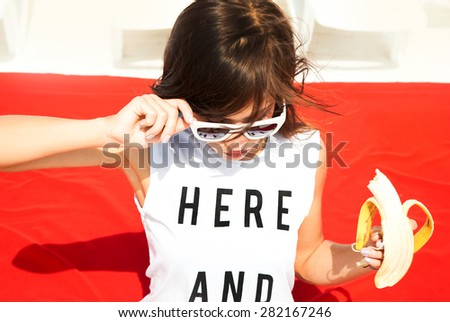 Young stylish sexy pretty hipster girl having fun, on the beach,and eating fruits. Funny image of  woman eating big banana and having fun.Sunshine sunglasses,Hare and now  - stock photo
