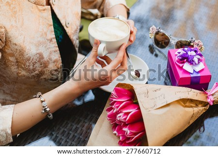 young stylish woman, fashion sunglasses, sitting in cafe, holding drinking cup cappuccino, tulips, happy birthday party, boho outfit, europe vacation, romantic dinner, gift, close up, detail - stock photo
