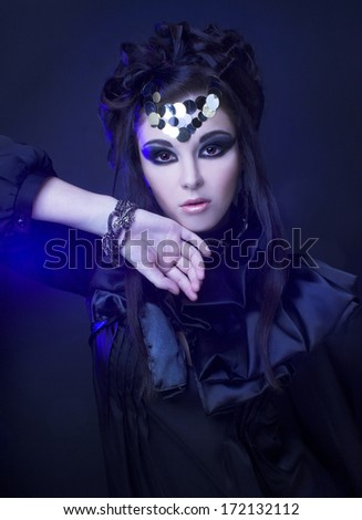 Young stylish woman in black dress with artistic visage with smokey-eyes standing  in blue light - stock photo