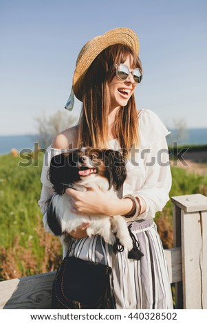 young stylish woman in countryside, holding a dog, happy positive mood, summer, straw hat, bohemian style outfit, sunglasses, smiling, happy, sunny - stock photo