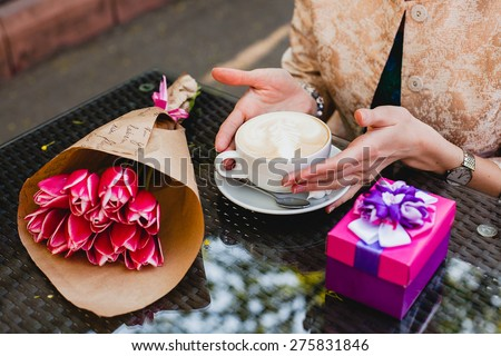 young stylish woman, sitting in cafe, holding drinking cup cappuccino, smiling, enjoying warm, presents, tulips, happy birthday party, city street, europe vacation, detail, close up - stock photo