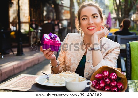 young stylish woman, sitting in cafe, holding present box, tulips, happy birthday party, city street, europe vacation, glamour outfit, romantic dinner, smiling, looking, cappuccino cup, cake