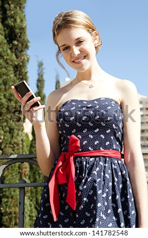 Young stylish woman using a smartphone while standing on a city bridge, smiling at the camera during a sunny day with a blue sky.