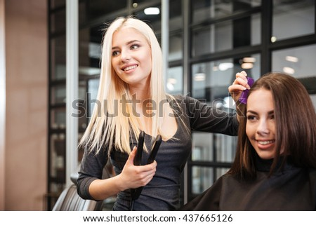 Young stylist with styling iron straightening woman hair at beauty salon