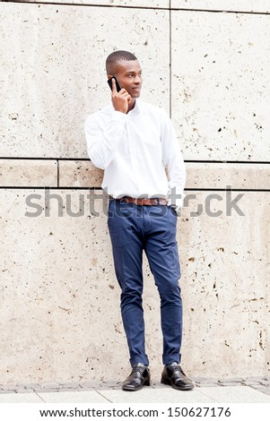 young successfil african businessman with mobilephone talking walking outdoor - stock photo