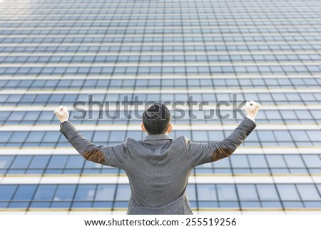 young successful asian businessman with urban background,modern glass building - stock photo