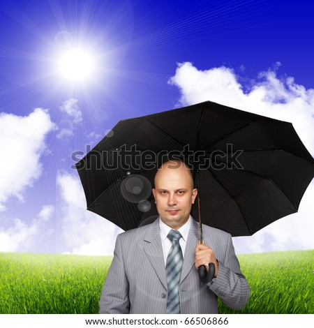 Young successful business man with a black umbrella against the sky