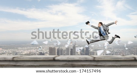 Young successful businessman jumping against city background - stock photo