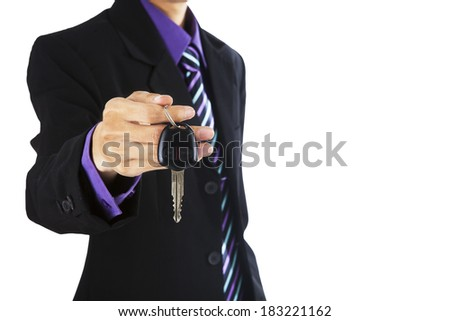 Young successful businessman offering a car key - stock photo