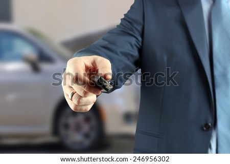 Young successful businessman offering a car key.  - stock photo