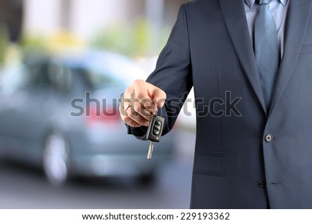 Young successful businessman offering a car key. Close-up of driver's hand showing key - stock photo
