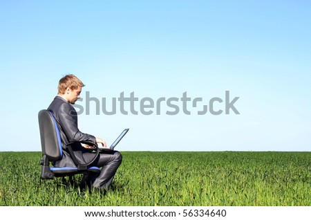 Young successful businessman, on the green meadow - stock photo